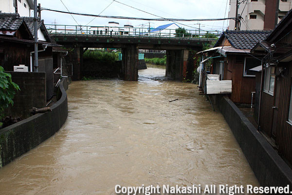 増水した川と民家