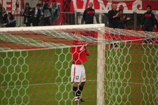 051 ユニの左胸のエンブレムを掴み、サポーターを指さすロビーのゴールパフォーマンス